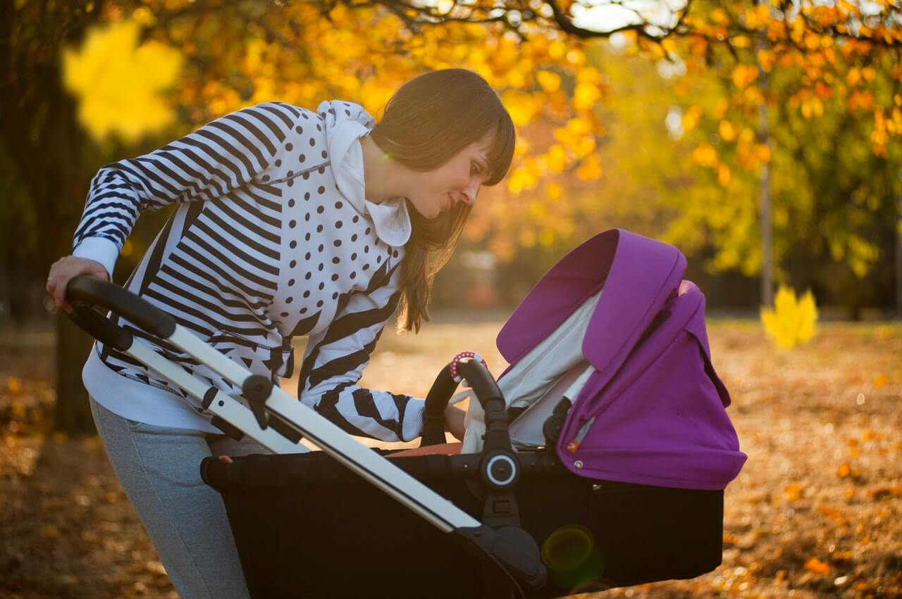 Photo of mum in park leaning over baby in pushchair